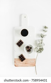Coffee cup and dark chocolate on vintage marble cutting board with eucalyptus branch on white background. Flat lay, top view breakfast concept.