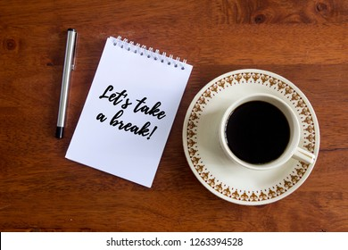 A coffee cup for drinking, a pen and notepad on wooden office desk written with text Let's take a break!. Flat lay shot.