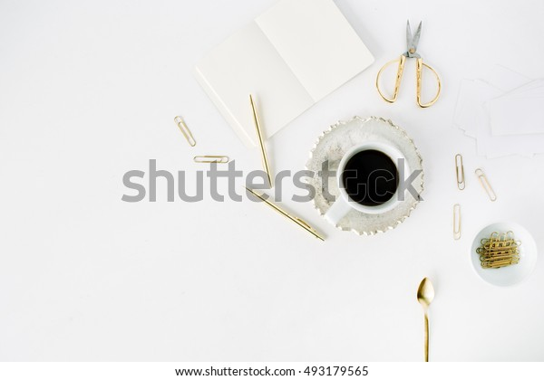 coffee cup, empty diary and golden accessories: tea spoon, pen, clips and scissors on white background. flat lay, top view