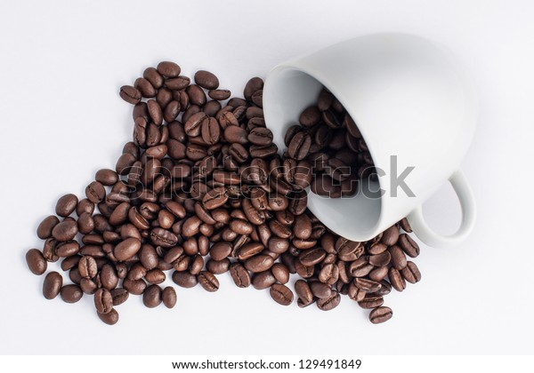 a coffee cup filled with coffee and beans with jute on white background