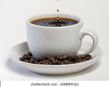 Coffee cup filled with hot fresh coffee with a drip of coffee being poured in
