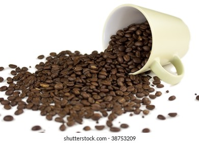 A coffee cup filled with whole coffee beans turned over and spilled out