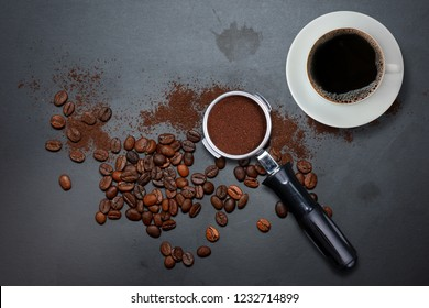 Coffee cup and filter holder of espresso with grounds and scattered roasted coffee beans on dirty black table with coffee stains background, top view. Fresh coffee and porta filter with grounds