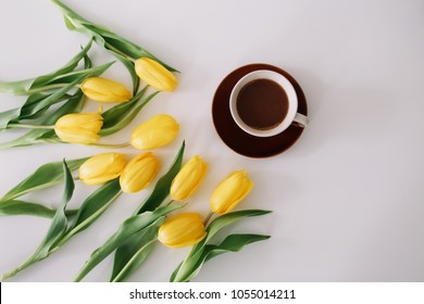 A coffee cup in a frame of yellow tulips on white background. Flat lay, top view. Concept of holiday, birthday, Easter, March 8.