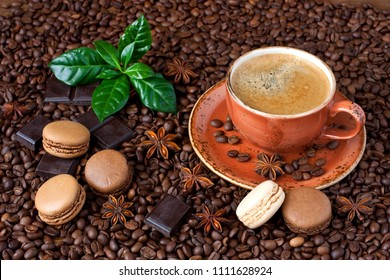 Coffee cup, french macaroons, dark chocolate  and fresh leaves on coffee beans background