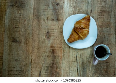 Coffee cup and fresh baked croissants on wooden background. Top View. Example of a breakfast