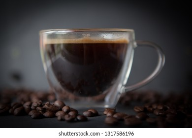 Coffee cup with fresh brewed coffee and brown roasted coffee beans scattered on dark stone background side view