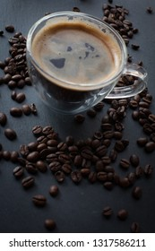 Coffee cup with fresh brewed coffee and brown roasted coffee beans scattered on dark stone background top flat lay view