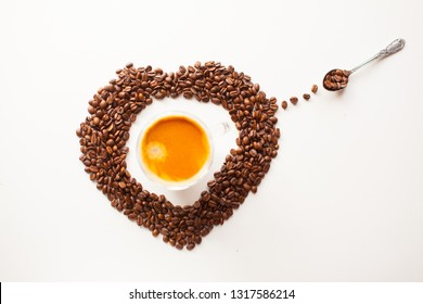 Coffee cup with fresh brewed coffee and brown roasted coffee beans in a heart shape on white background top flat lay view