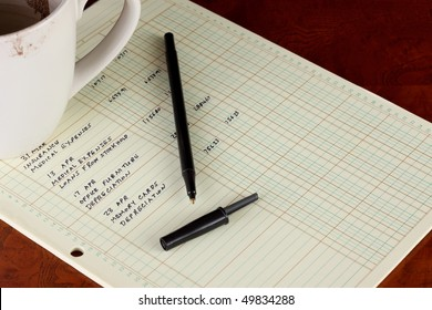 Coffee cup with general ledger sheet showing journal entries and black ballpoint pen on polished wooden table top