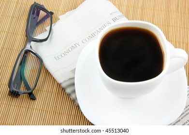 Coffee cup with glasses and newspaper on wooden background