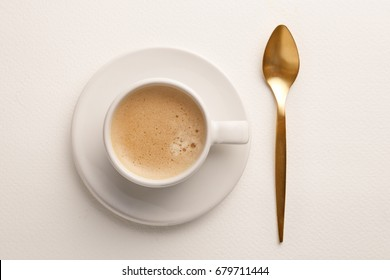 Coffee cup and golden spoon viewed from directly above. White background. Top view