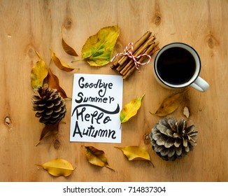 Coffee cup and goodbye summer,hello Autumn text on a note on rustic wooden table with Autumn leaves ,cinnamon and pine cone
