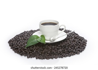 ?white coffee cup and green leaf(leaves) on the coffee beans isolated white at the studio.