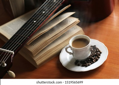 Coffee cup and guitar on wooden table, white steam