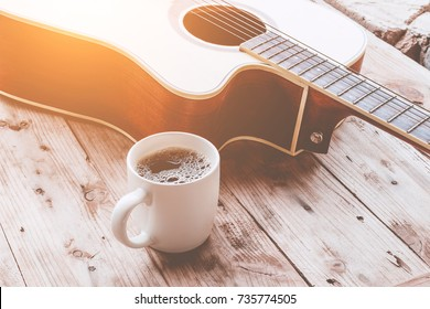 Coffee cup and guitar on wooden table.vintage tone.