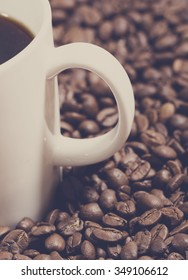 A coffee cup handle from a cup filled with black coffee and some coffee beans next to it. Image has a vintage effect and tones applied. Image taken on a wooden table.