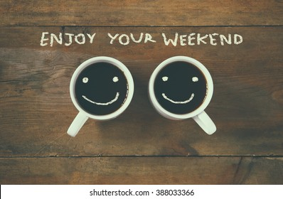 "coffee cup with happy faces next to ""enjoy your weekend"" phrase background. vintage filtered. happy weekend concept"