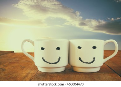 coffee cup with happy faces over wooden table in front of blue sky. vintage filtered. happy weekend concept