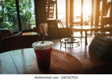 Coffee cup of hot ice americano on wood table in coffee shop background.