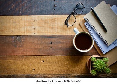 Coffee cup hot and notebook pen laptop on wooden table desk