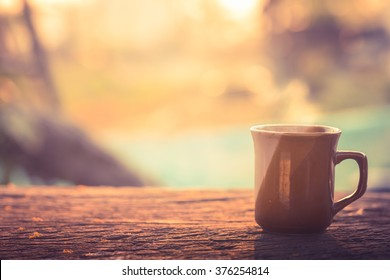 Coffee cup with hot coffee on old wood table in sunlight & blur green nature background