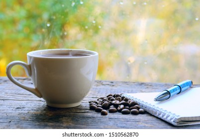 A coffee cup with hot coffee is on the table. Near coffee beans. Notepad with a vintage pen. Blurred background. Daylight from the window. Concept - Business Morning Breakfast