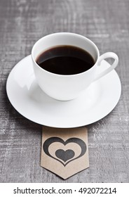 Coffee cup hot white on wooden board with heart label. Grey wood