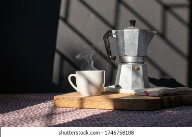Coffee cup and Italian coffee maker over table, under morning light. Wood tray, hot smoke from cup. At home morning rituals concept. Lifestyle food background.