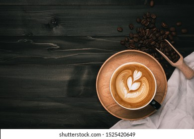 Coffee cup with latte art and beans on old wood table.there is space for ads,text,design and advertisement.