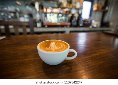 Coffee cup with latte art on wooden table . Selective focus white cup.color vintage style.blur coffee shop background