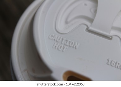 A coffee cup lid against a dark wooden background on a cold morning. The lid has a caution hot warning.