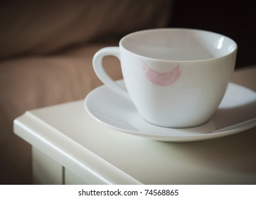 coffee cup with a lipstick mark on rim on a bedside table