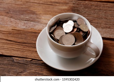 Coffee cup with lots of coins