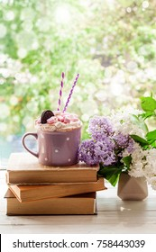 Coffee cup with marshmallow, open book and flowers bouquet on window sill. Feminine background. Breakfast, reading, spring and education concept
