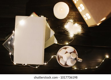 Coffee cup with marshmallows and a book on the table. Still life on dark background.  Top view, flat lay
