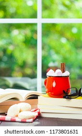Coffee cup with marshmallows, books and cookies on window with blur green garden