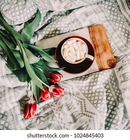 Coffee cup with marshmallows and red tulips in bed. Concept of holiday, birthday, Easter, March 8.  flat lay