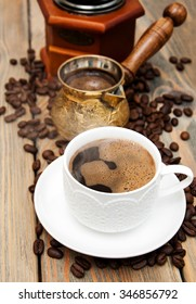 coffee cup,  metal turk and coffee beans on a wooden background