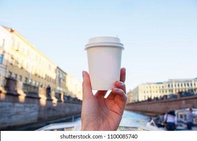 Coffee cup mock up. A coffee to go on the backgroung of sity. Hand holding paper cup with empty logotype circle  on a ship traveling along a canal.