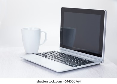 Coffee cup next to open laptop computer on white studio background