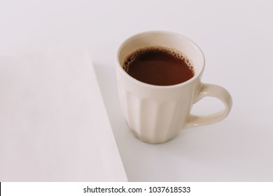 A coffee cup and a notebook. Business breakfast  on white background. Flat lay, top view, office desktop, lifestyle image.
