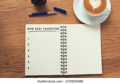 Coffee cup and notebook with new years resolution on rustic desk from above, planner and checklist concept.