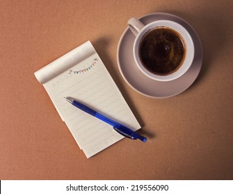 coffee cup with notebook on table