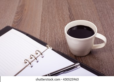 Coffee cup with notebook on wood background.