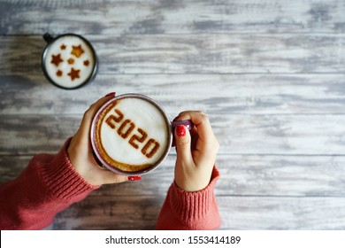 Coffee cup with number 2020 on frothy surface in female hands holding over grey painted wood plank background and another cup with star symbols on frothy surface. Happy new year 2020 food art theme.