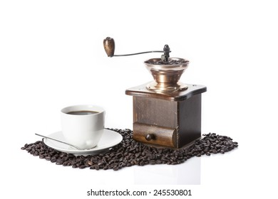 A coffee cup and old(vintage, classic) grinder on the coffee isolated white at the studio.