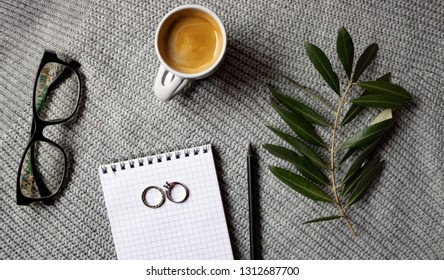 Coffee cup, olive branch, glasses, notepad and pencil on the gra