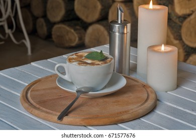 Coffee cup on bar table and romantic candles closeup with wooden logs background
