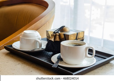 coffee cup, on black wooden tray.